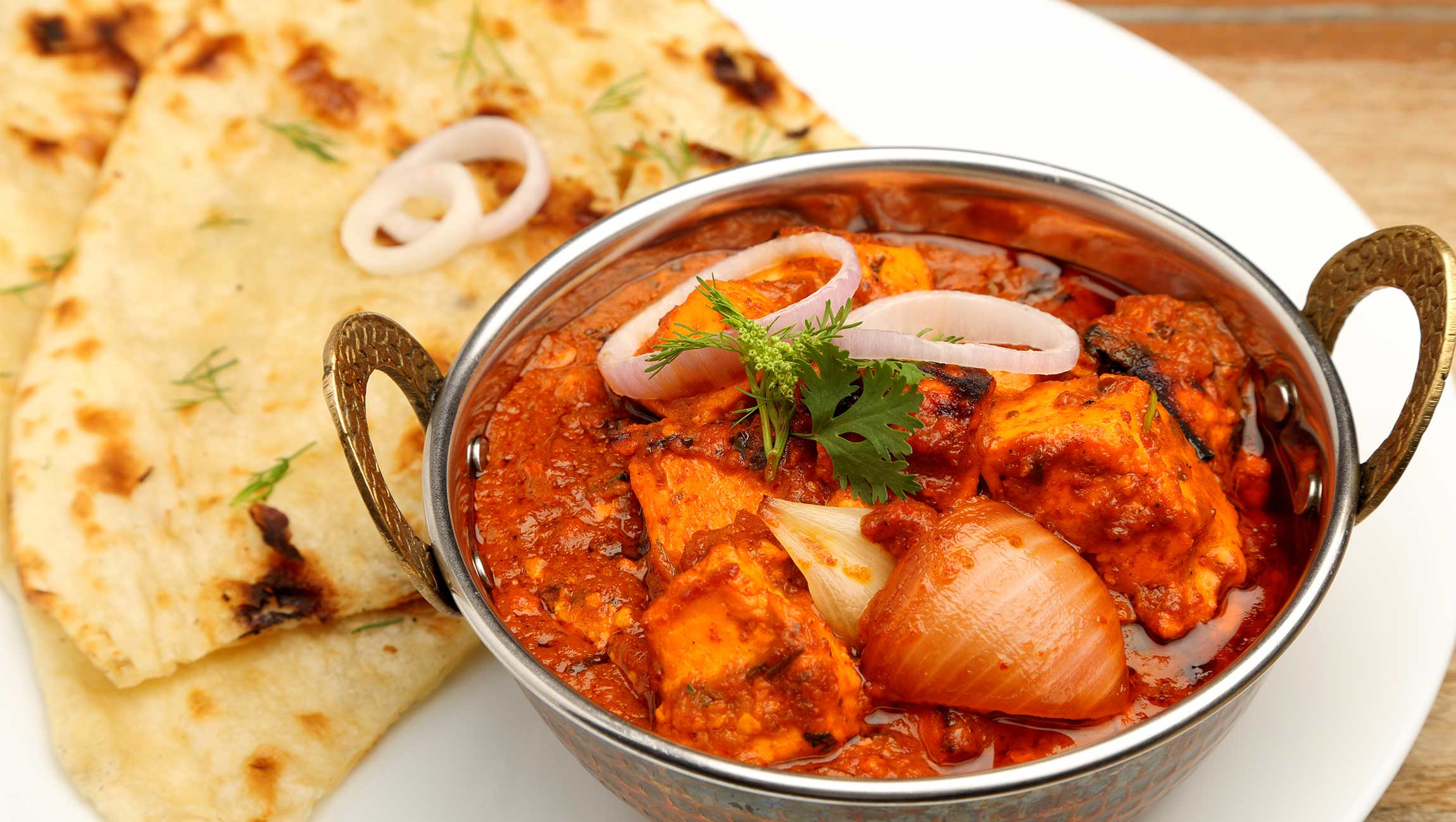 traditional indian curry on plate with naan bread